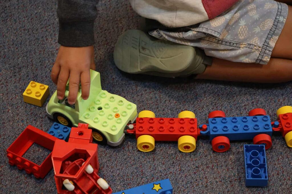 Child's hand is pushing toy car with trailers on floor of early childhood centre.