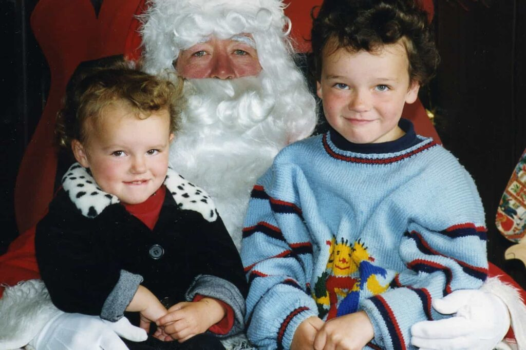 Children sitting on Father Christmas' knee.