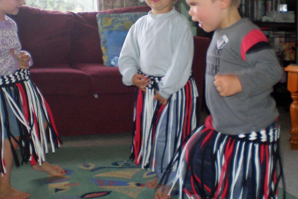 Children wearing Maori skirt costumes having fun practising haka