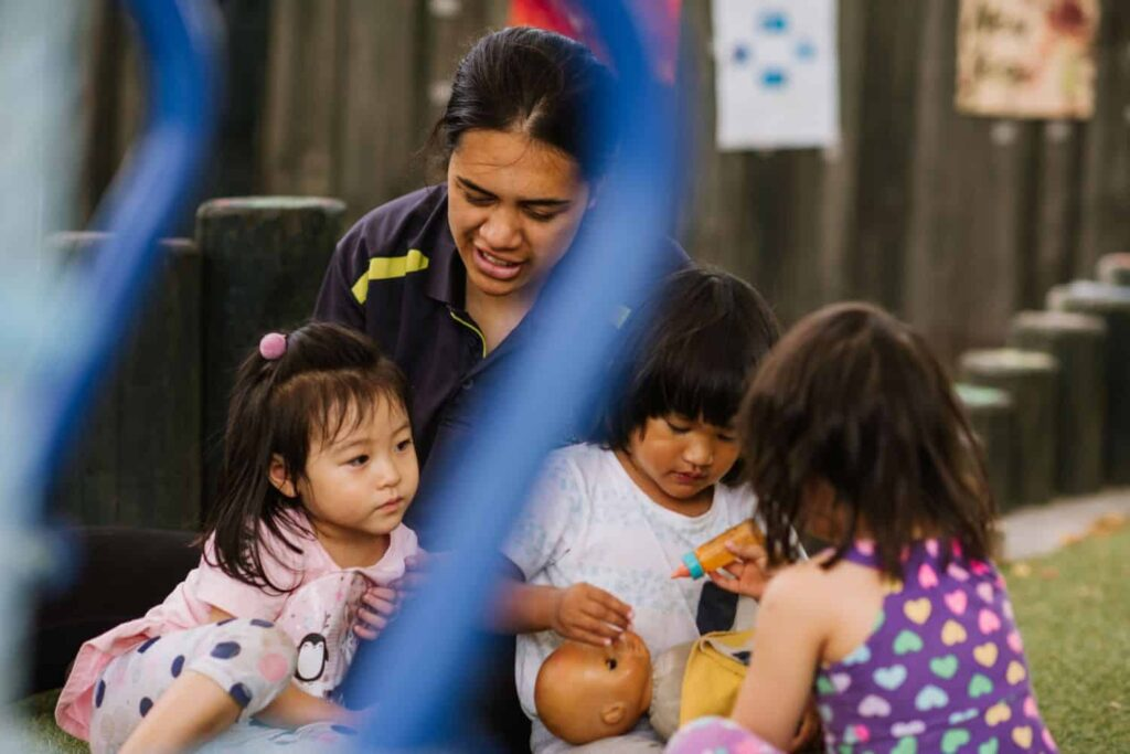 Teacher with girls in outside playground who are feeding their baby doll