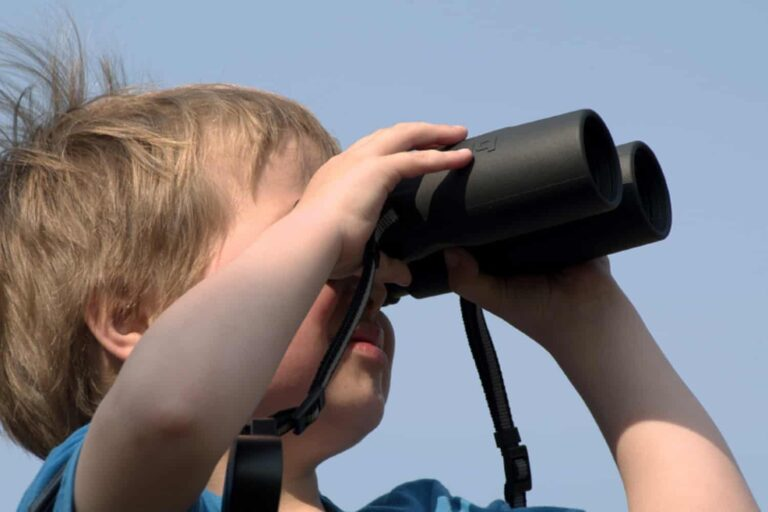 child with binoculars looking out