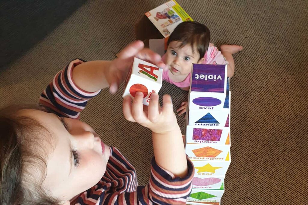 Young toddler with infant looking on, builds a tower of square blocks as tall as herself.