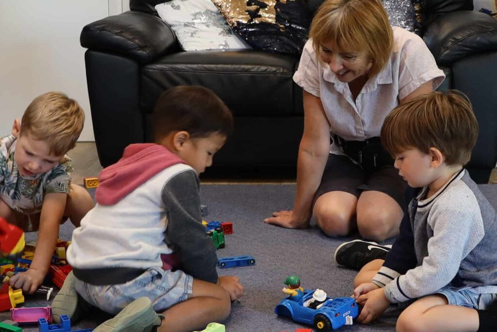 Teacher and three boys are playing with Duplo block toys on mat at early childhood centre.