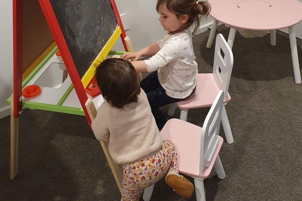 Toddler and pre-schooler children sitting at kindy chalk board.