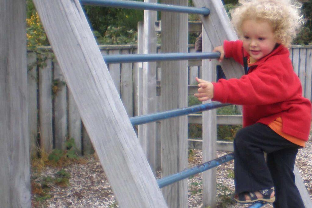 child climbing ladder of fort in ECE playground
