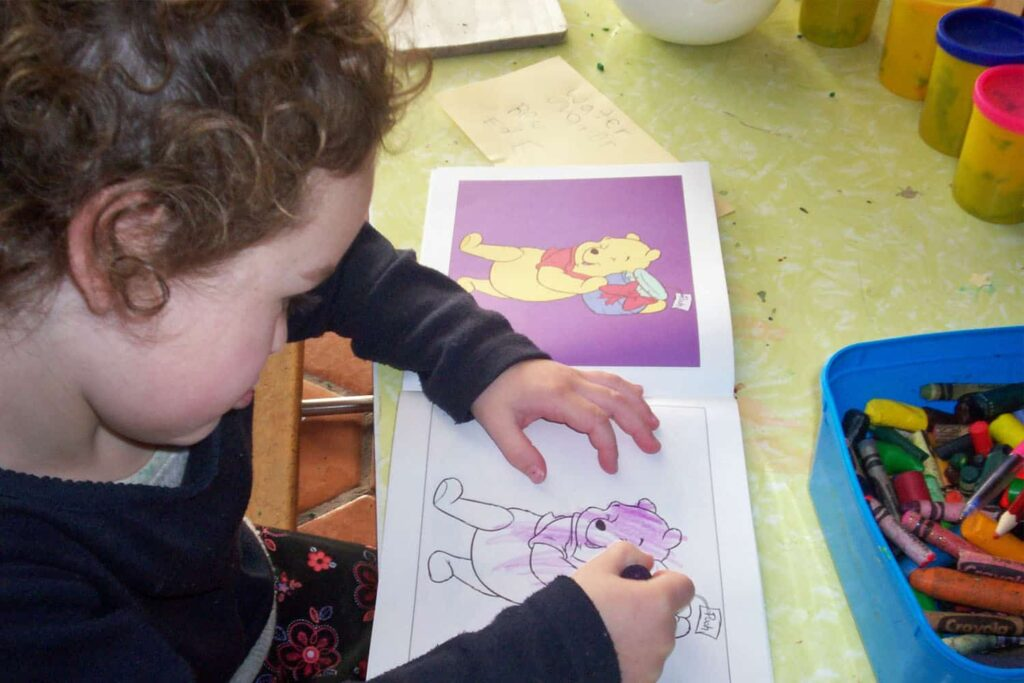 child is drawing in colouring-in book
