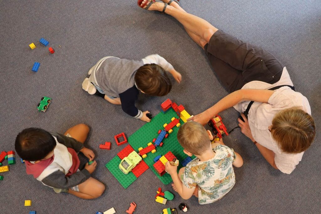 teacher with children on mat early learning curriculum