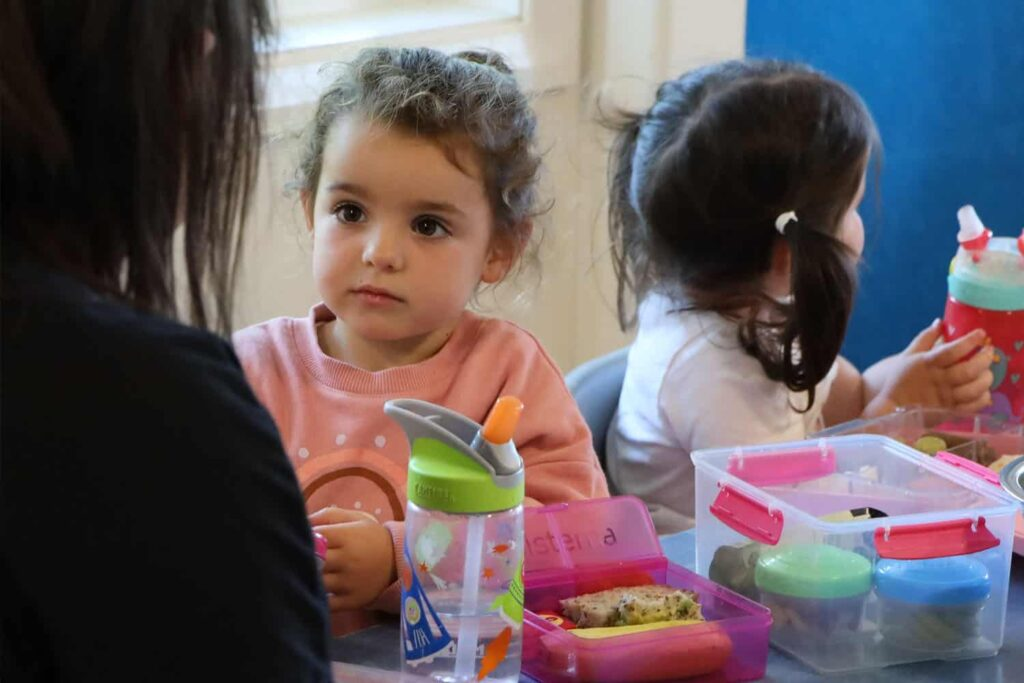 Child and teacher talking at lunch-time table in early childhood centre.