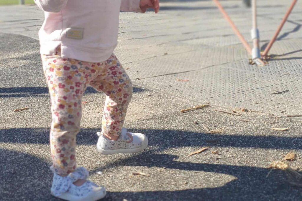 toddler walking on concrete and over to safety surface at playground.