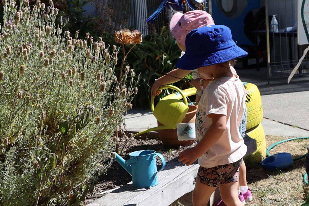 Children watering garden in summer