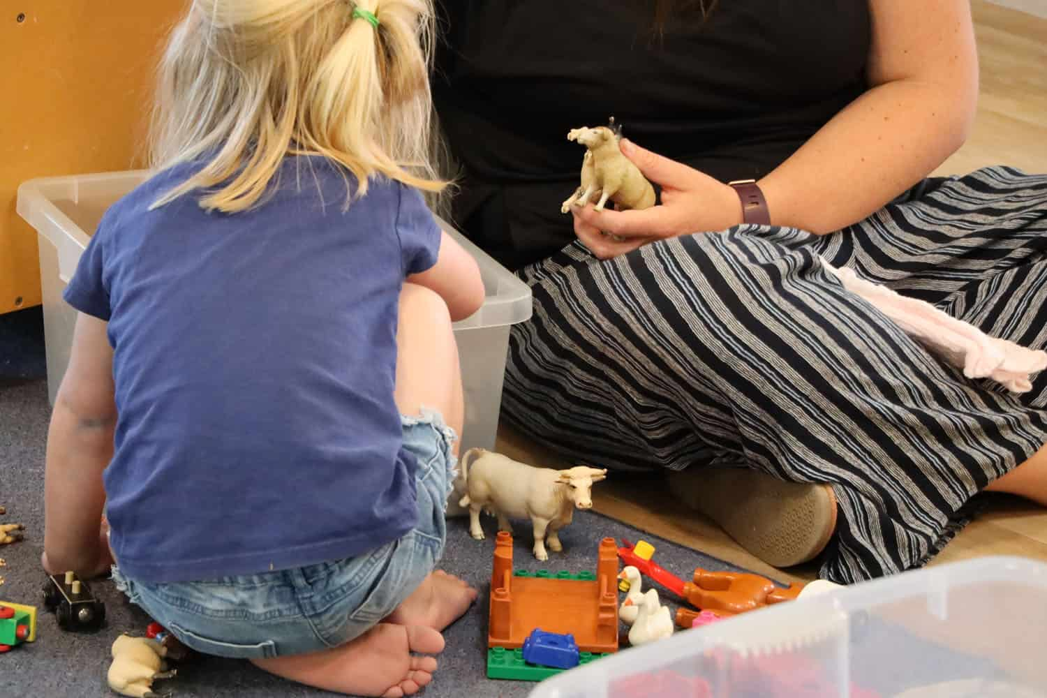 Child and teacher playing with toy farm animal block set.