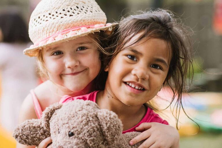 Two friends at early childhood centre smiling and playing together holding a teddy-bear.