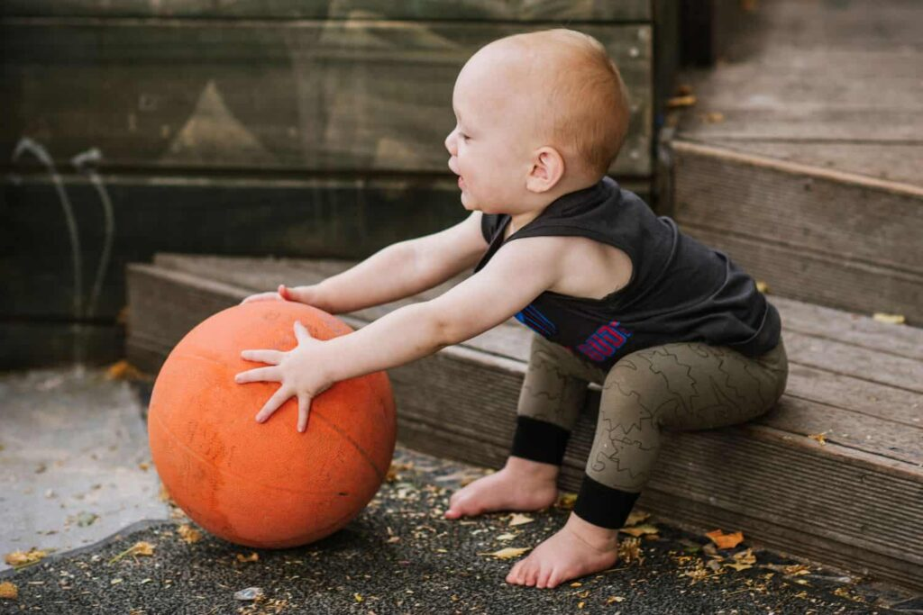Infant holds large ball at early childhood centre