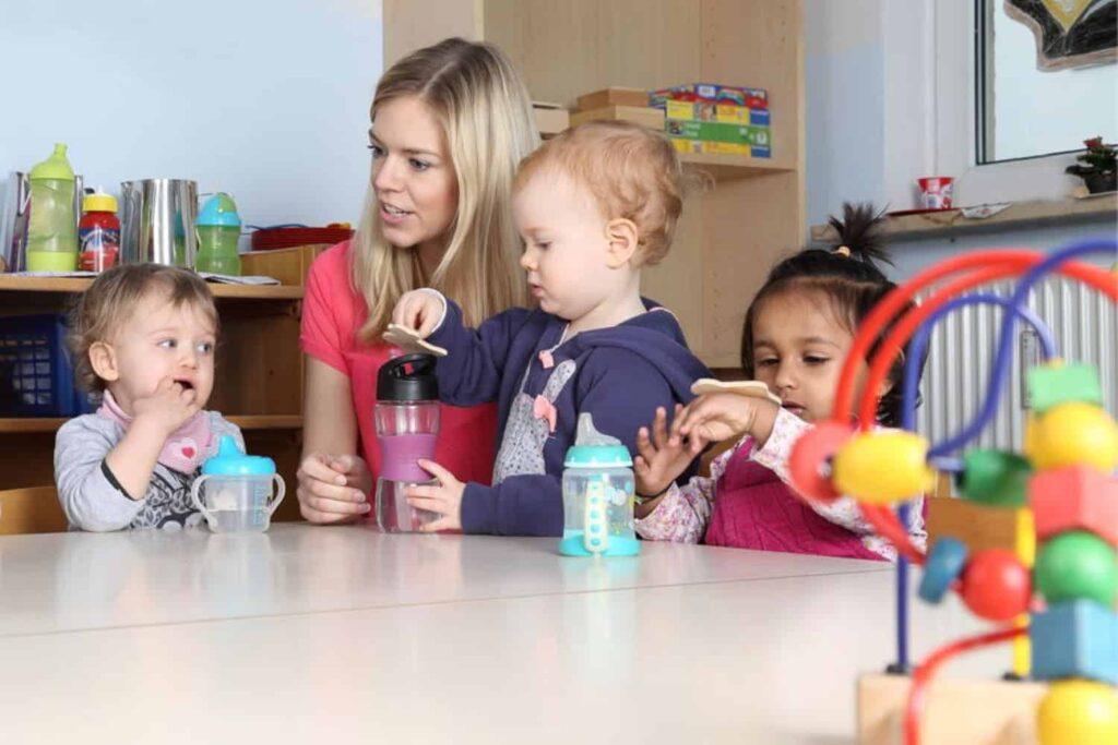 teacher at table with children having a drink