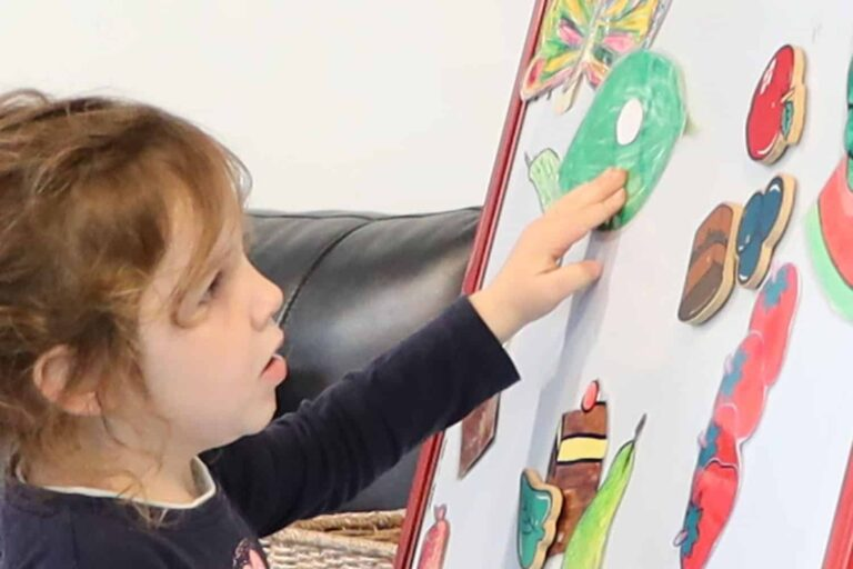 Child tells the story of the hungry caterpillar to friends at ECE centre