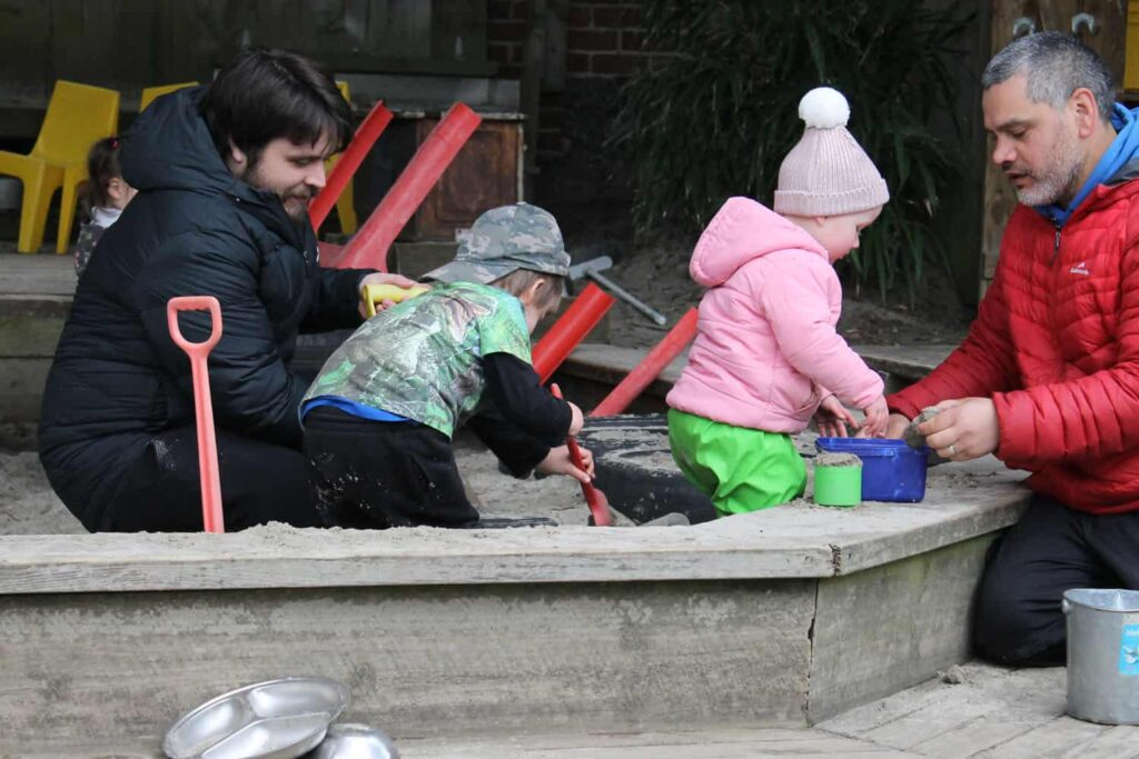 male teachers and children playing and learning in sandpit at early childhood centre.