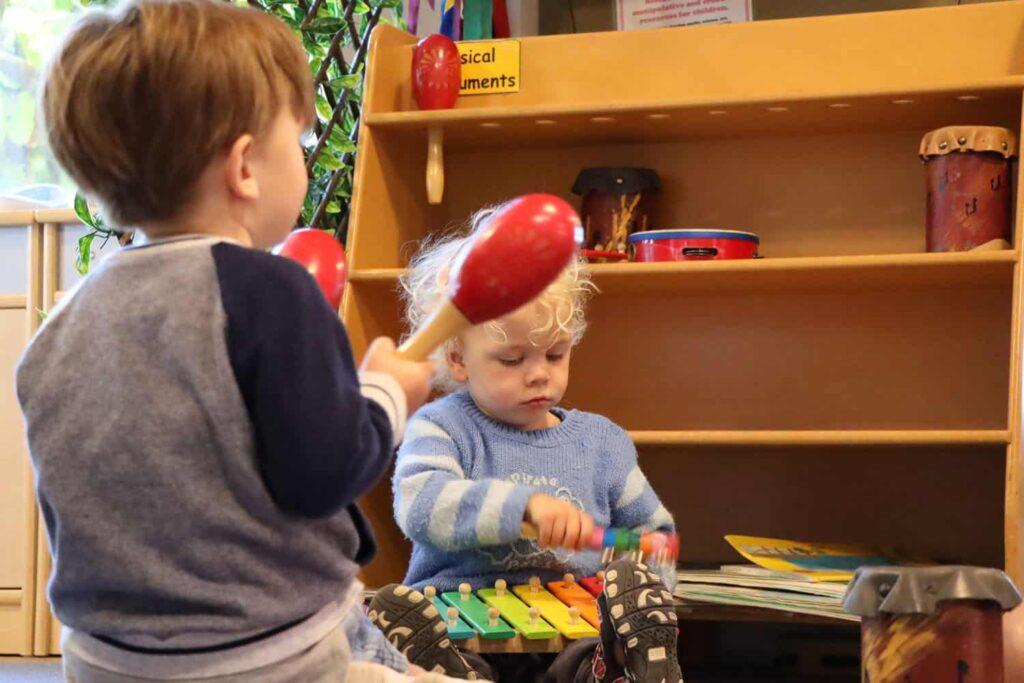 Young children making music at kindergarten.
