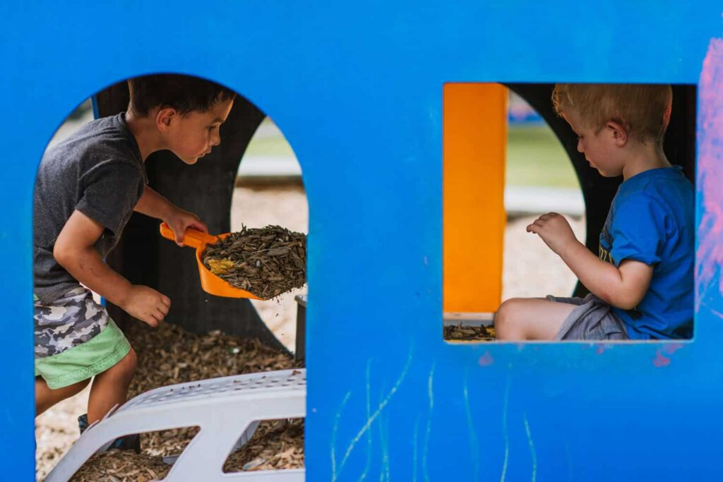 Boys playing outside co-operatively in box with bark chips in early childhood playground.