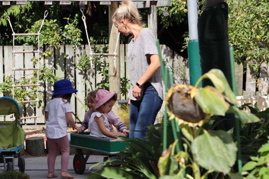 Teacher with happy children playing outside at early childhood centre on summer day.