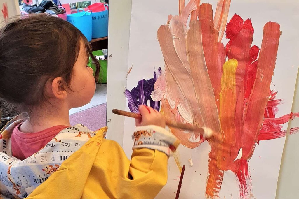 child with paint brush paints brightly coloured picture at kindergarten