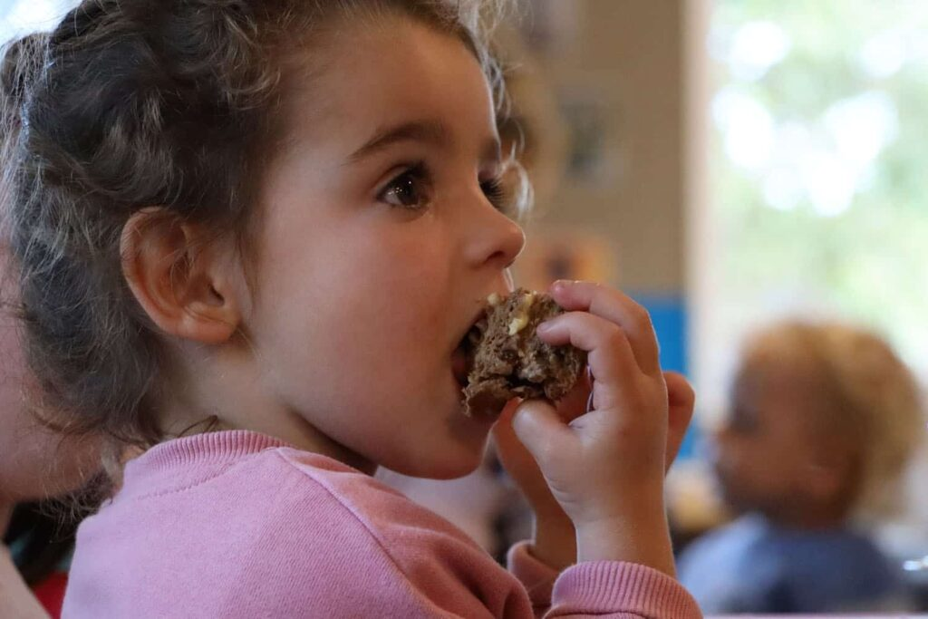 child eating a muffin at an early childhood centre
