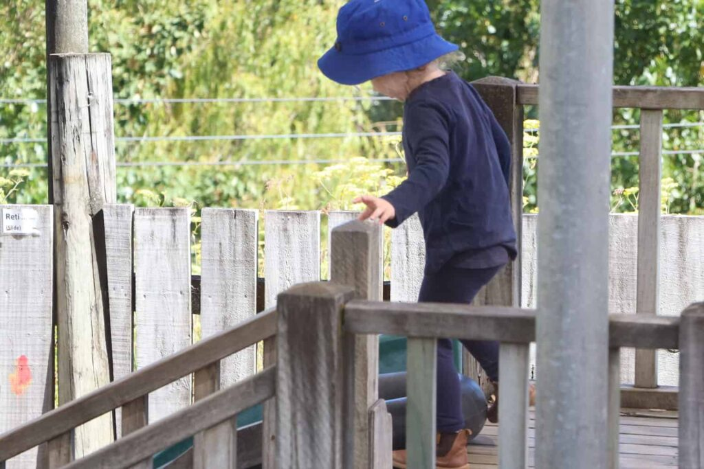 child up high on wooden fort at early childhood centre
