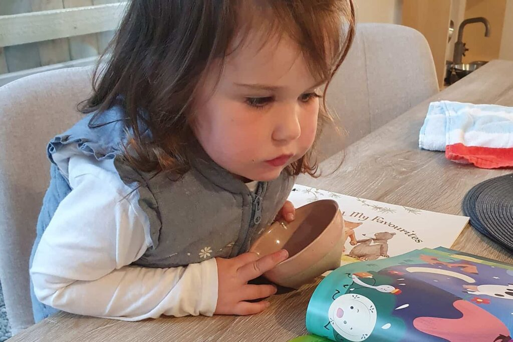 young toddler reading book at kitchen table while having a snack