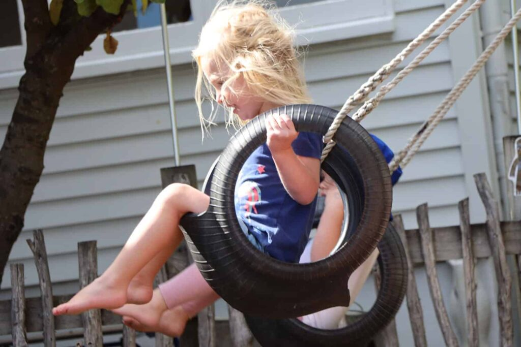 child swinging high on swing in playground of NZ early childhood centre
