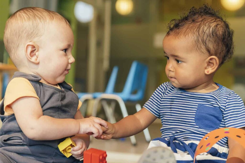 two toddlers touch hands
