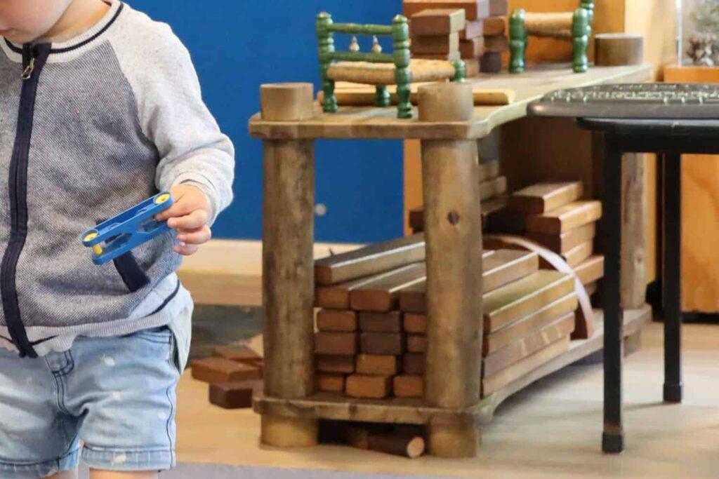 toddler with preschool wooden blocks shown in background