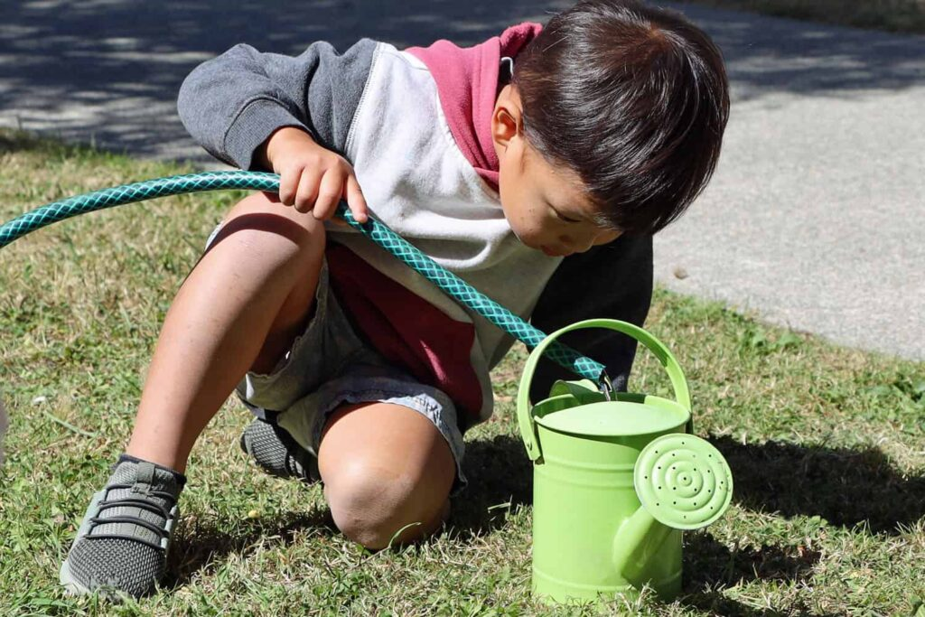 child filling watering can using hose