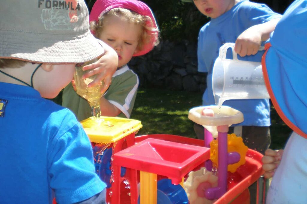 sun protection and children with sunhats engaged in waterplay in home-based ECE